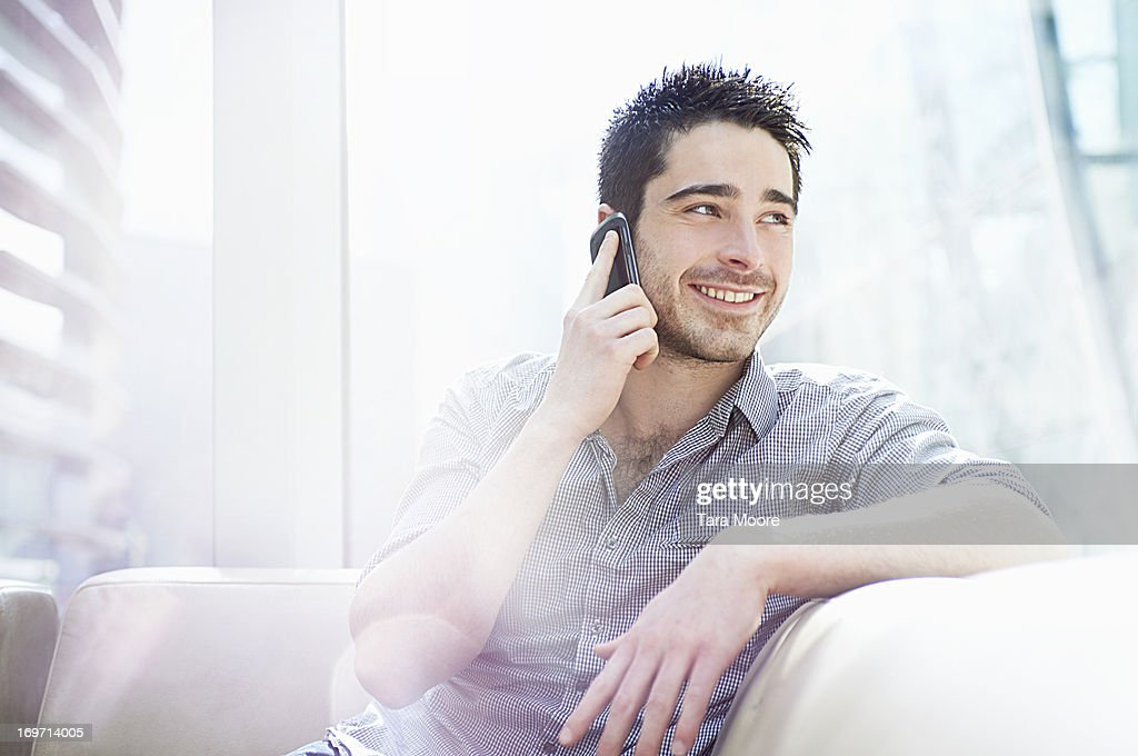 man talking on mobile in office and smiling : Stock Photo