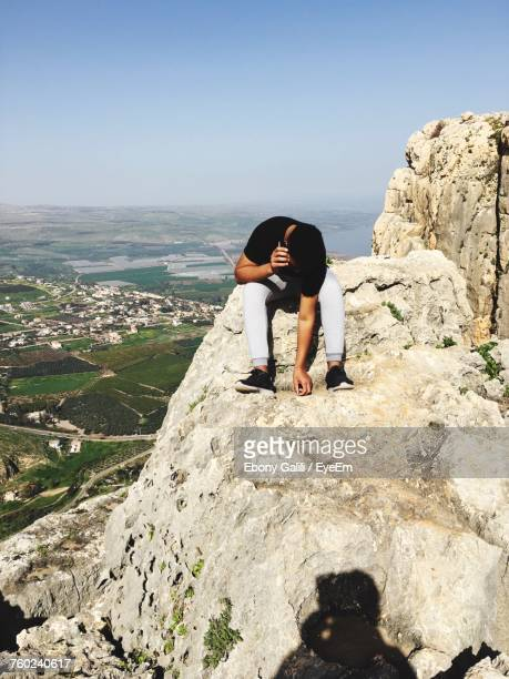 Man Talking On Mobile Phone While Sitting On Cliff At Mount Arbel