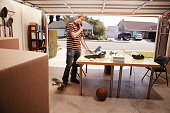 Man talking on phone in office space in garage