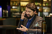 Cheerful man drinking wine in restaurant and calling on phone