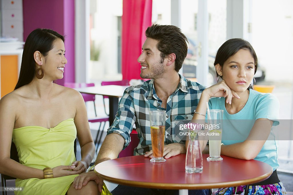 Man talking to a woman while their friend looking away : Stock Photo