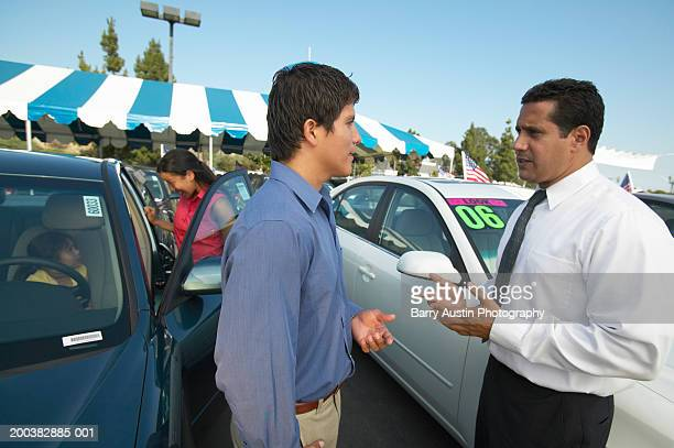 Man talking to car salesman, family in background looking at car
