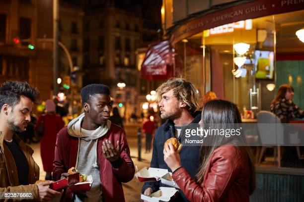 Man talking to friends while having burger in city