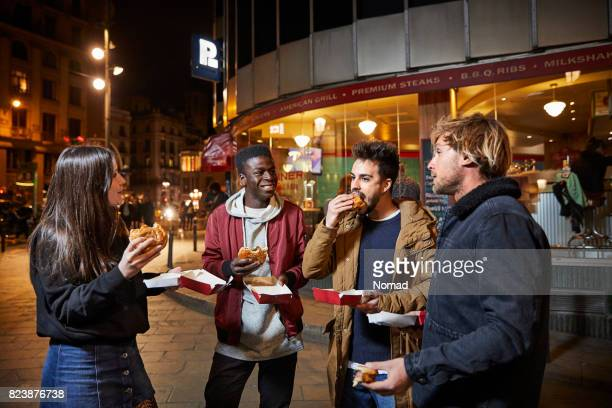 Homme de parler à des amis tout en ayant des hamburgers