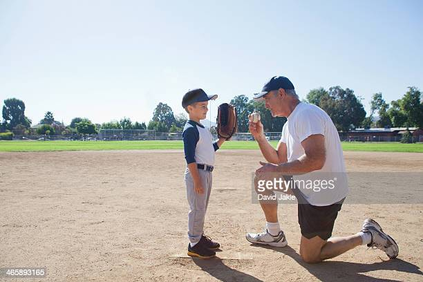 Man talking to grandson on baseball field
