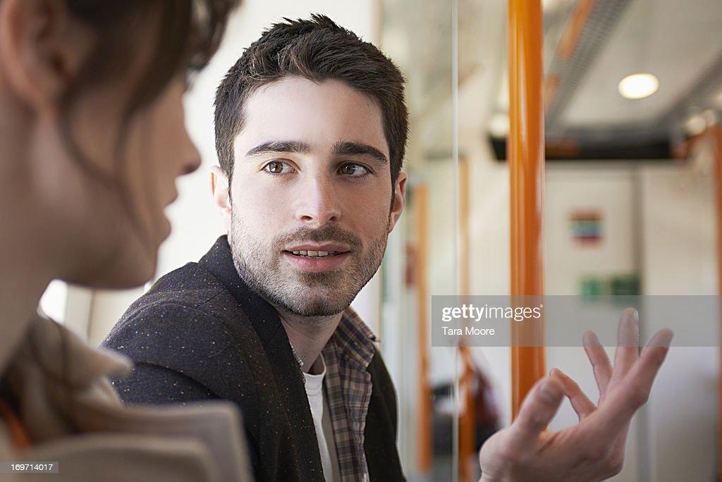 man talking to woman in train : Stock Photo