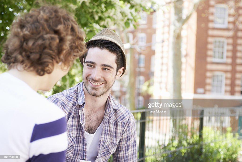 man talking to woman outside : Stock Photo