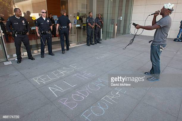 A man talks at officers at Los Angeles Police Department Headquarters near a chalk message calling for the release of the video from the body cameras...