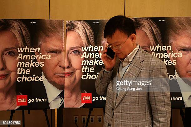 A man talks his mobile phone in front of banners of Democratic presidential candidate Hillary Clinton and Republican presidential candidate Donald...