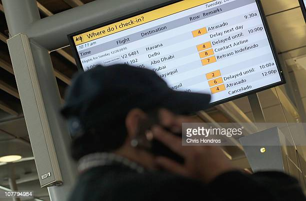 A man talks on a cell phone under a display screen listing canceled and delayed flights at Terminal 4 of John F Kennedy International Airport...