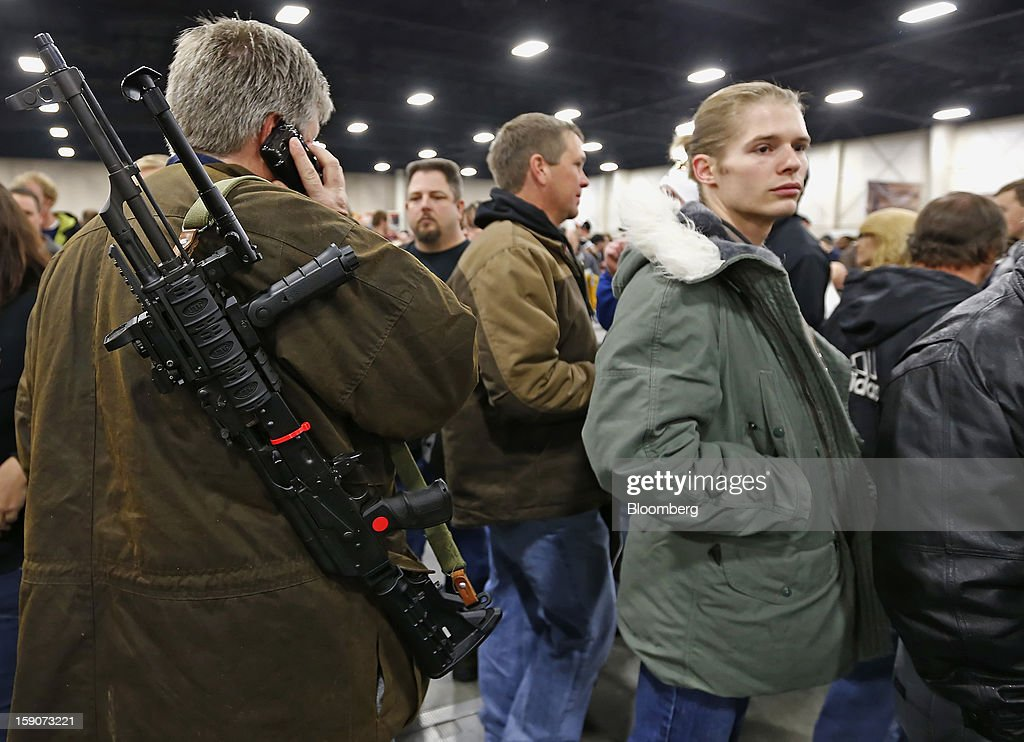 A man talks on a cell phone while carrying a semi-automatic assault rifle he is trying to sell at the Rocky Mountain Gun Show in Sandy, Utah, U.S., on Saturday, Jan. 5, 2013. A working group led by Vice President Joe Biden is seriously considering measures that would require universal background checks for firearm buyers, track the movement and sale of weapons through a national database, strengthen mental health checks and stiffen penalties for carrying guns near schools or giving them to minors. Photographer: George Frey/Bloomberg via Getty Images
