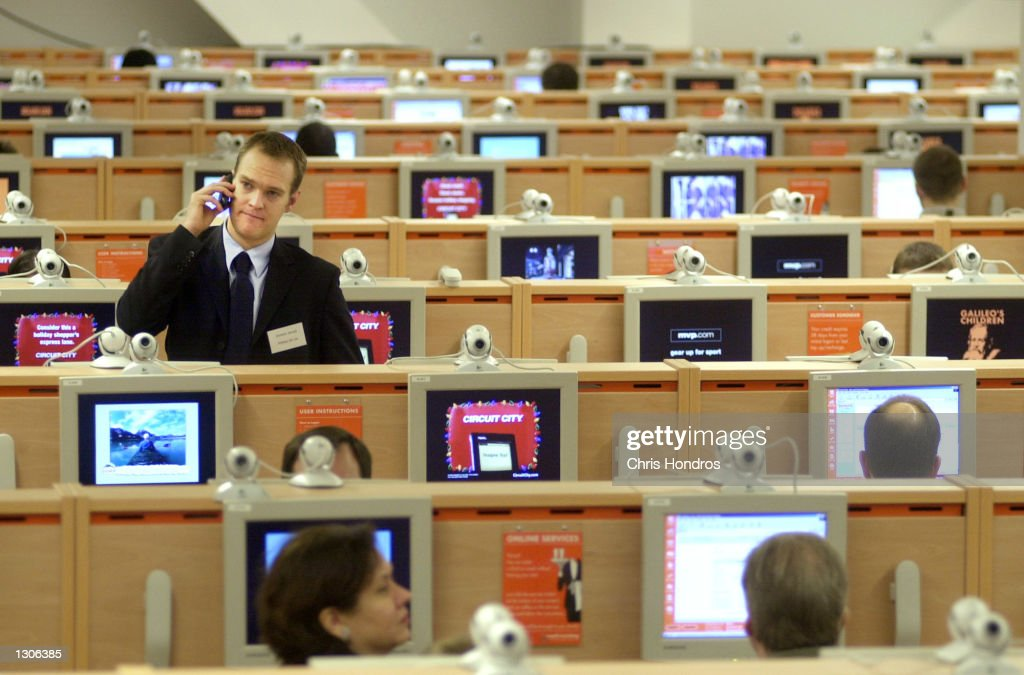 A man talks on a mobile phone among computer terminals on opening day at the easyEverything Internet cafe November 28 2000 in Times Square New York...