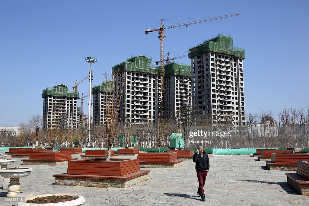A man talks on a mobile phone as he walks past residential buildings under construction at the Sino-Singapore Tianjin Eco-city in Tianjin, China, on Wednesday, March 13, 2013. China's money-market rate rose to a one-week high after central bank Governor Zhou Xiaochuan said yesterday the nation should be on 'high alert' over inflation. Photographer: Tomohiro Ohsumi/Bloomberg via Getty Images