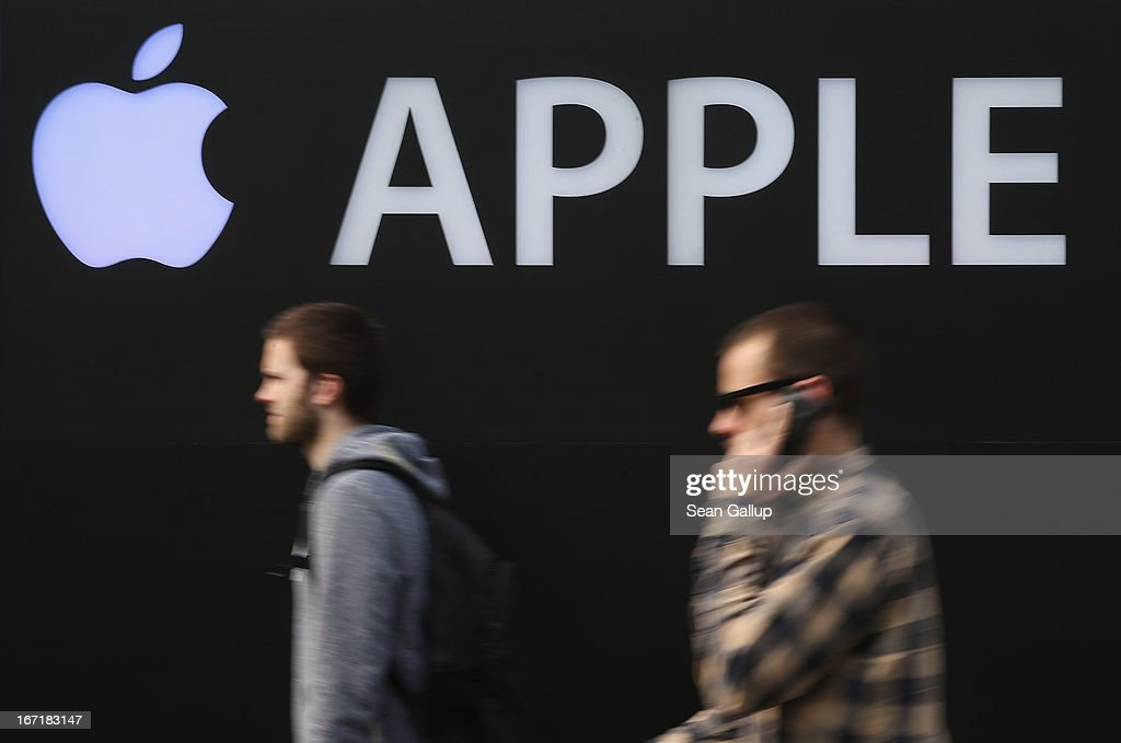 A man talks on a mobile phone as he walks past the construction site of the new Apple Store on Kurfuerstendamm avenue on April 22, 2013 in Berlin, Germany. The store is due to open in May and will the be the first Apple Store to open in the Germany capital.