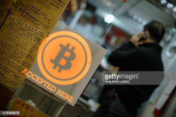 A man talks on a mobile phone in a shop displaying a bitcoin sign during the opening ceremony of the first bitcoin retail shop in Hong Kong on...