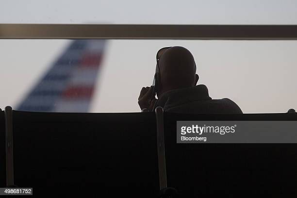 A man talks on a mobile phone in front of an American Airlines Group Inc airplane at Ronald Reagan National airport in Washington DC US on Wednesday...