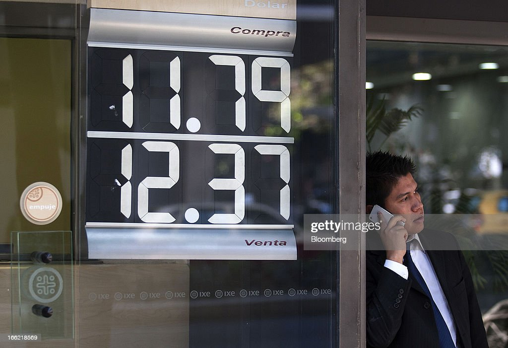 A man talks on a mobile phone next to a currency exchange rate window display at an Ixe branch near Avenue Reforma in Mexico City, Mexico, on Tuesday, April 9, 2013. Mexico's peso rose to the strongest since August 2011 after a report showed faster-than-forecast inflation last month, damping speculation that policy makers will cut interest rates to slow the currency's advance. Photographer: Susana Gonzalez/Bloomberg via Getty Images