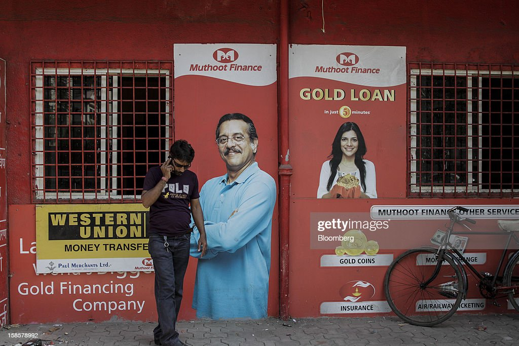A man talks on a mobile phone outside a Muthoot Finance Ltd. branch in Mumbai, India, on Tuesday, Dec. 18, 2012. Muthoot Finance Ltd. is India's biggest lender that uses gold jewelry as collateral. Photographer: Dhiraj Singh/Bloomberg via Getty Images