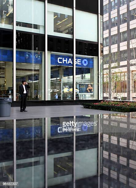 A man talks on his mobile phone outside a JPMorgan Chase Co bank branch in New York US on Wednesday April 14 2010 JPMorgan Chase Co said a...