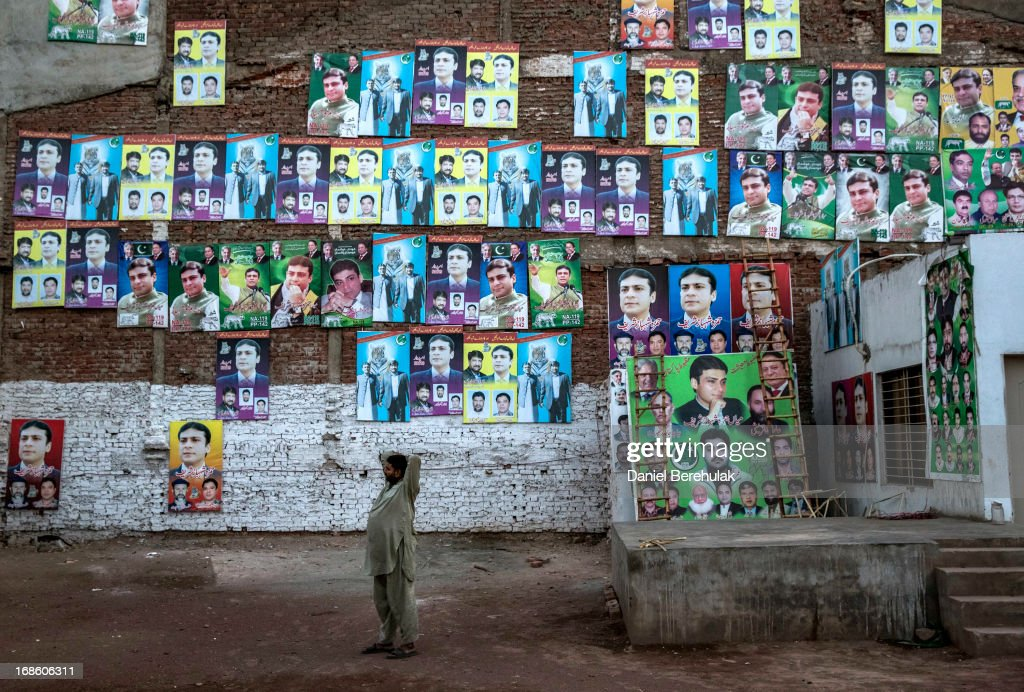 A man talks on his phone as he stands in front of a wall pastered wth PML-N party election campaign posters the day after election day on May 12, 2013 in the Old City of Lahore, Pakistan. The electoral committee recorded a high voter turn out as millions of Pakistanis cast their votes in yesterdays parliamentary elections. It is the first time in the country's history that an elected government will hand over power to another elected government. Initial results show the PML-N party has recorded the highest number of seats won and party leader.Nawaz Sharif has claimed victory ahead of the last official results.