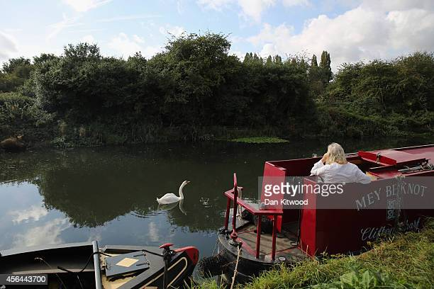 A man talks on his phone while sitting on his house boat on the Grand Union Canal on October 1 2014 in London England The disappearance of teenager...