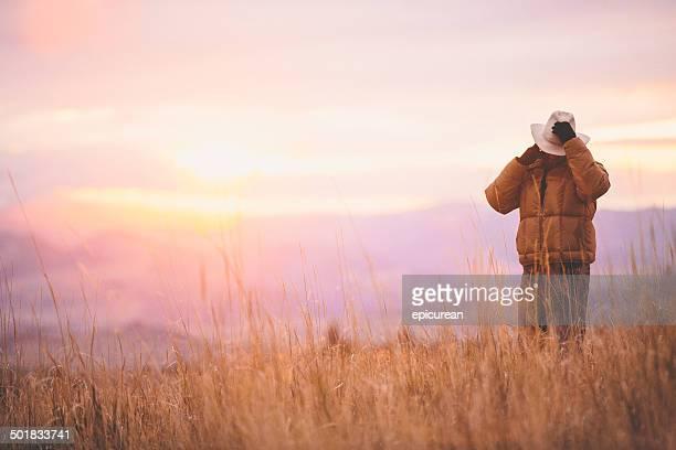 Man talks on phone while sun sets over mountain range