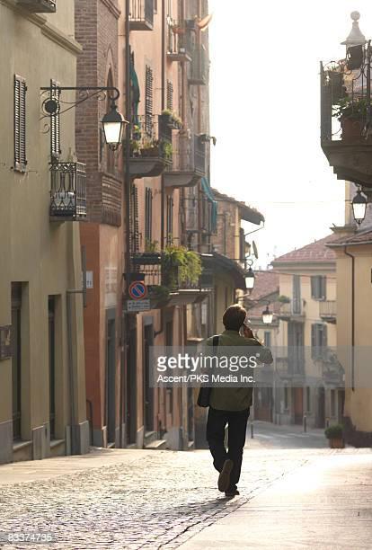 Man talks on phone while walking along cobblestone