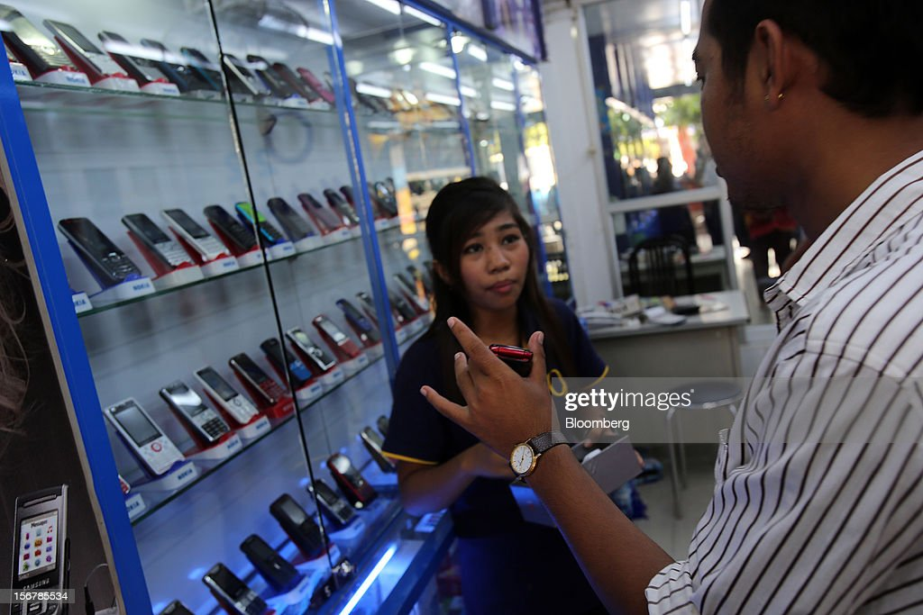 A man talks to a store attendant at a mobile phone store in Yangon, Myanmar, on Tuesday, Nov. 20, 2012. Myanmar's growth outlook has improved 'substantially' amid political reforms, which are expected to lead to a large influx of foreign investment, the Organization for Economic Cooperation and Development (OECD) said on Nov. 18. Photographer: Dario Pignatelli/Bloomberg via Getty Images