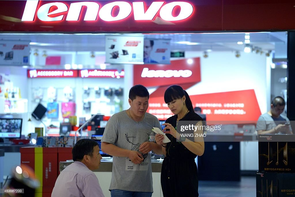 A man talks to a woman at the entrance to a Lenovo store in Beijing on August 14 2014 Lenovo on August 14 posted a 23 percent jump in quarterly net...