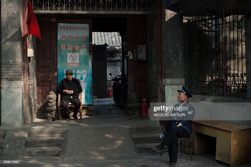 A man (L) talks with a security guard as they sit on a street in Beijing on April 29, 2016. / AFP / NICOLAS
