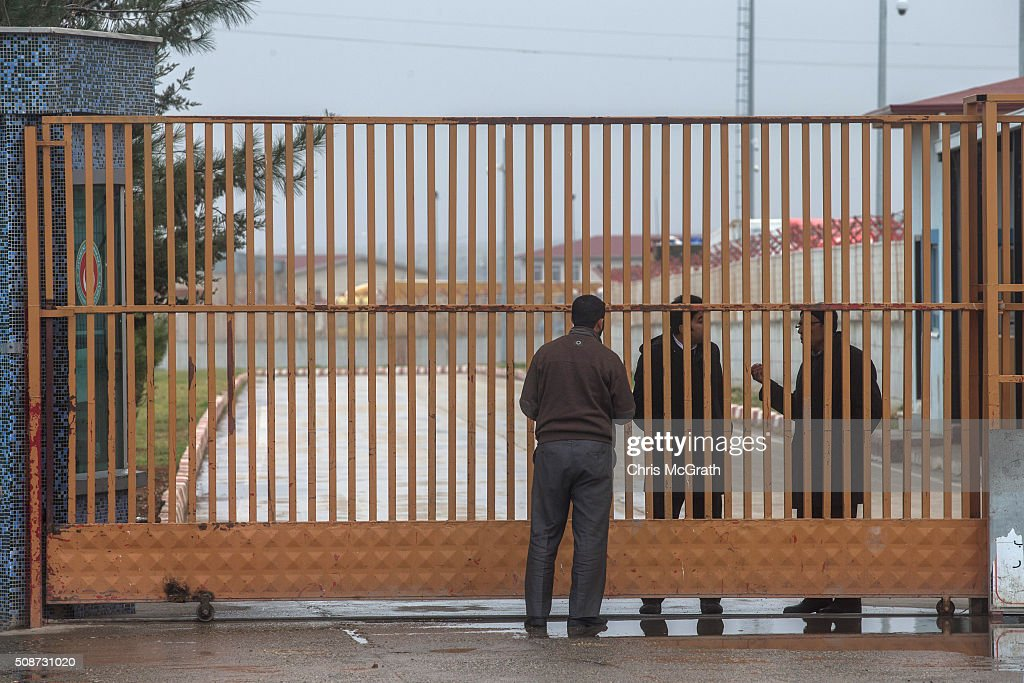 A man tallks with border control personel at the closed Turkish border gate on February 6, 2016 in Kilis, Turkey. According to Turkish officials some 35,000 Syrian refugees have massed on the Syrian/Turkish border after fleeing Russian airstrikes and a regime offensive surrounding the city of Aleppo in northern Syria.