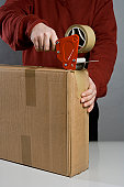 A man taping a cardboard box
