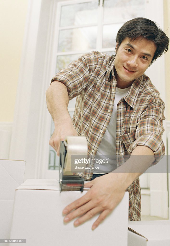 Man taping up box, portrait : Stock Photo