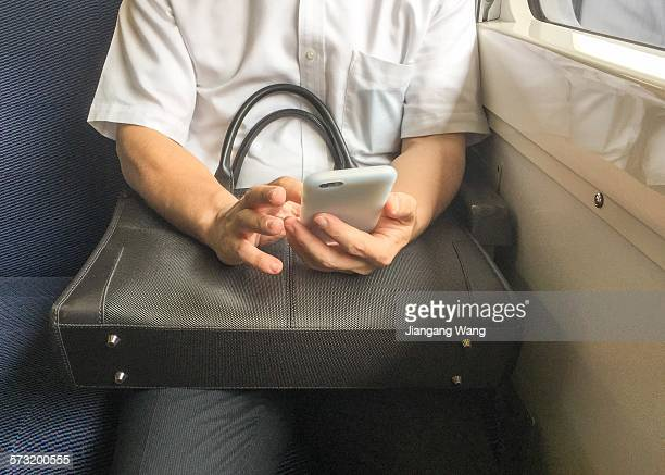 Man tapping on a smartphone in the seat of train