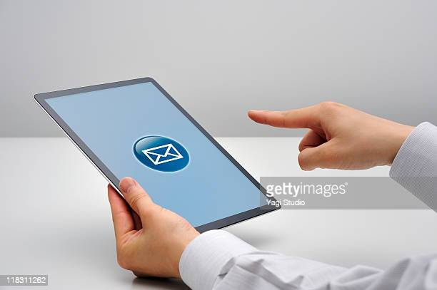 Man tapping on e-mail symbol on tablet computer