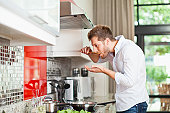 Man tasting food in kitchen