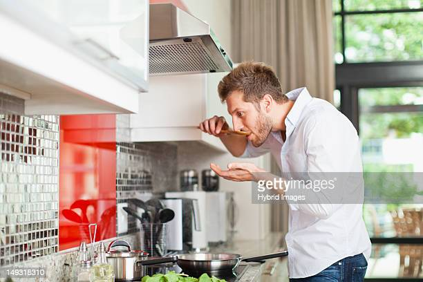 Man tasting food in kitchen