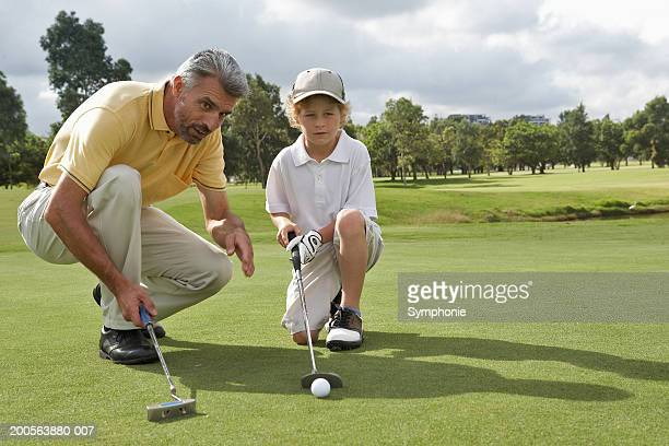 Man teaching boy (8-9) golf