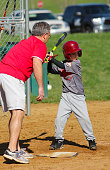A boy plays little league baseball and is taught proper technique by his coach.