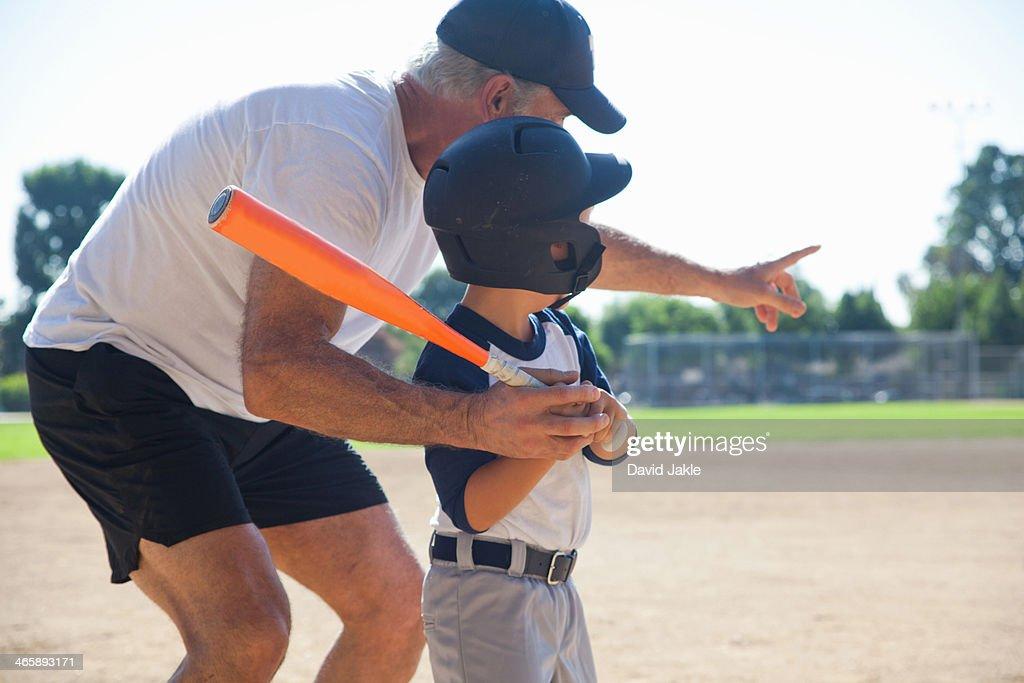 Man teaching grandson to play baseball