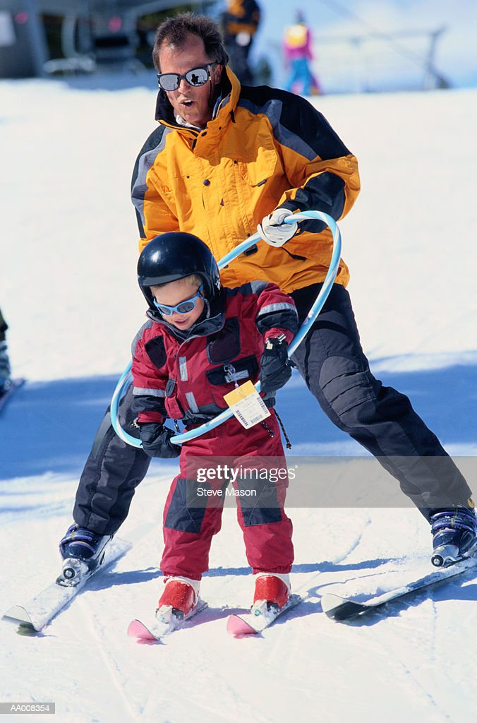 Man Teaching His Daughter to Ski Using a Hoop : Stock Photo