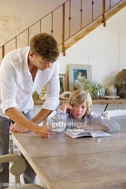 Man teaching his son at house