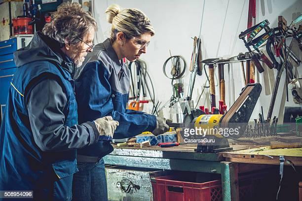 Homme enseigner femme Comment Mouture métal dans l'atelier de mécanique