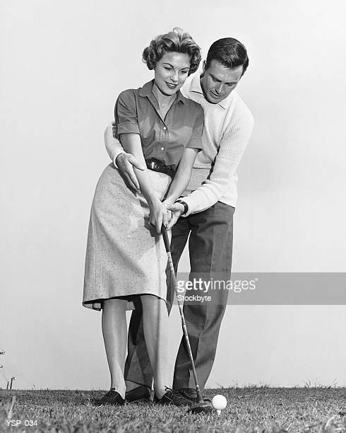 Uomo insegnare donna come battere golfball