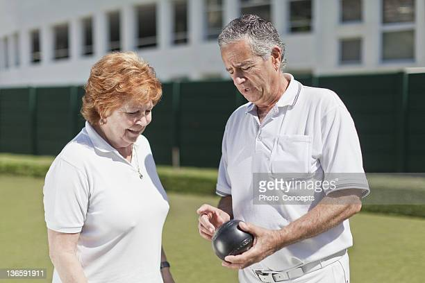 Man teaching woman lawn bowling
