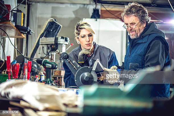 """Homme enseigner jeune femme en métal poli sur l """" atelier de mécanique"""