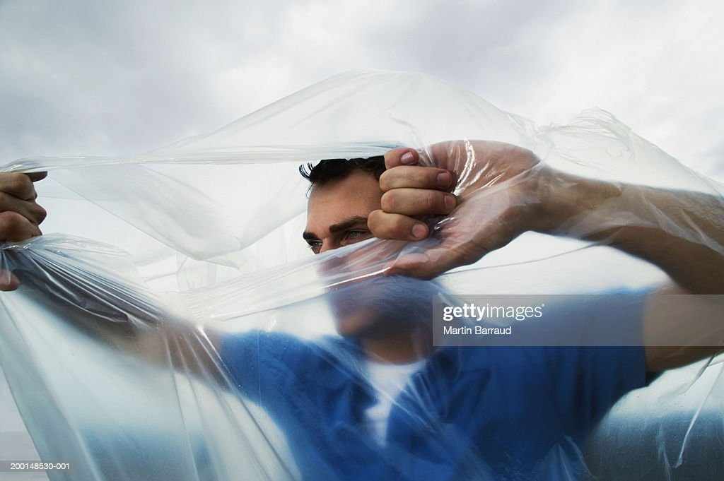 Man tearing hole in transparent bag from inside, outdoors : Stock Photo