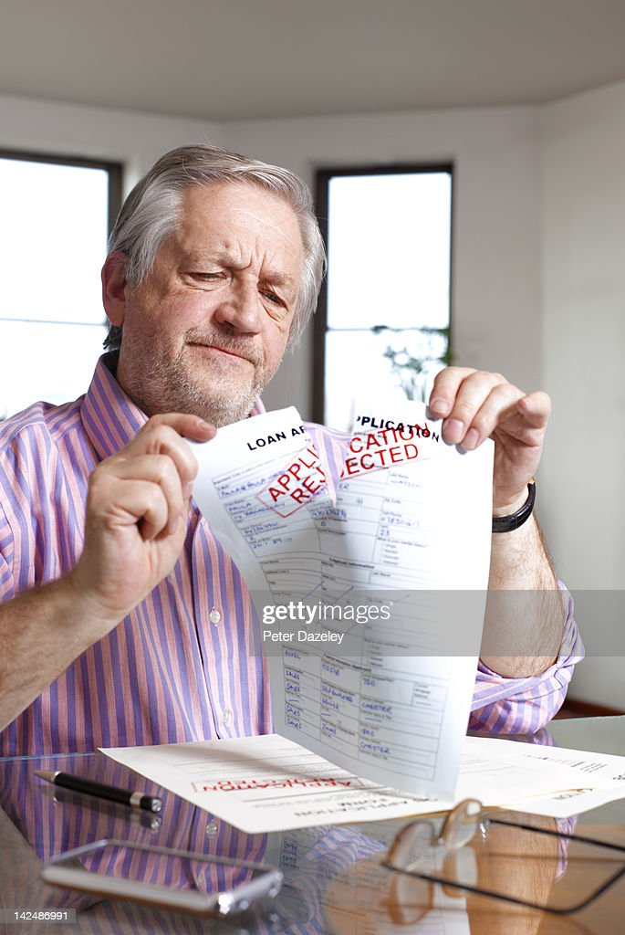 Man tearing up loan application rejection : Stock Photo