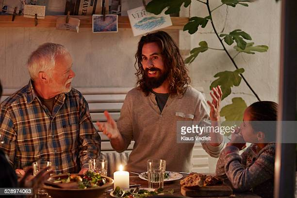 Man telling a story at family dinner in garden hou