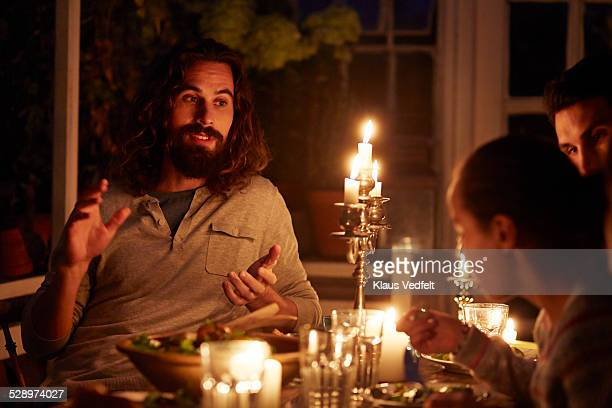 Man telling story at family dinner in gardenhouse